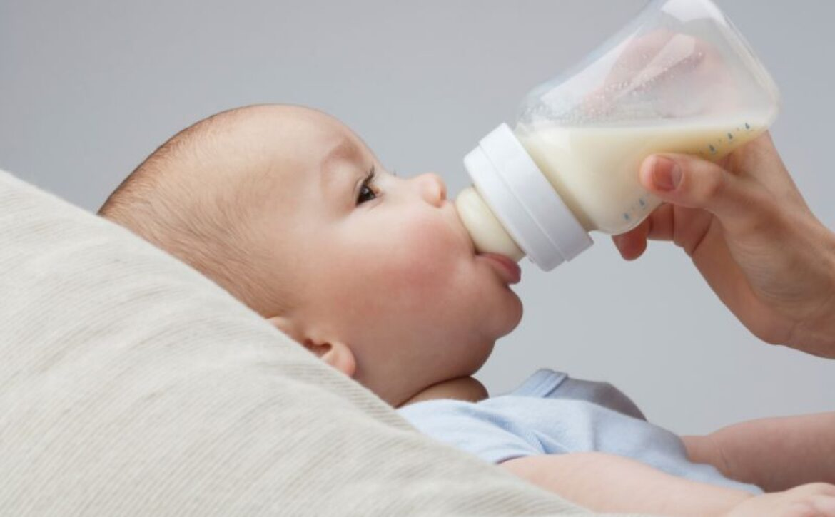 A baby being fed milk from bottle